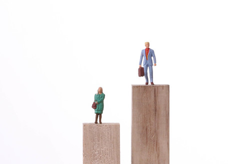 Miniature men and women standing on the different height block