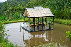 Glass House with Table and Chairs in the Middle of a Pond within Nature