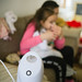 Mother treating her daughter at home with an inhalator.