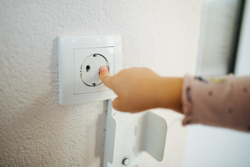 Young girl touching a protective outlet cover with her finger.