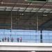 """Menschen vor dem BER Terminal 1 mit Schrift auf Glas """"Flughafen Berlin Brandenburg Willy Brandt"""""""