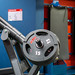 Bokeh Photo of Several Weight Plates on a Lat Pull Down Machine with Yoga Mats in the Background