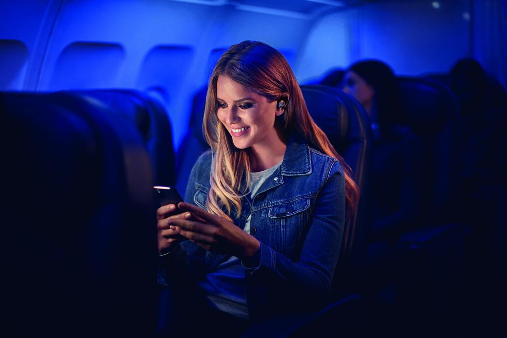 女性用戶在飛機上配戴Jabra Elite 85t 鈦黑款