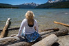 Blonde woman with back facing camera looks out to the Sawtooth Mountains while sitting on logs at Redfish Lake