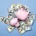 Broken piggy bank on a pile of US dollars