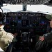 """Lt. Noah Smith, left, and Lt. Aman Bhatia, assigned to the """"Grey Knights"""" of Patrol Squadron (VP) 46, pilot a P-8A Poseidon anti-submarine warfare patrol aircraft during a training flight."""