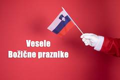 Santa Claus hand holding flag of Slovenia and text Vesele Božične Praznike
