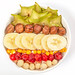 Top view, oatmeal breakfast with fresh fruits, hazelnuts and sun dried cherries on white background