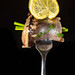 Pieces of marinated herring fish with green onion and lemon on fork, dark background