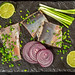 Top view, slices of marinated herring fillet with lime, green and purple onions on black stone tray