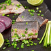 Marinated herring fillet with lime, green and purple onions on black, close-up