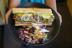 Person hält einen Teller in der Hand mit Pulled Pork Sandwich mit Schinken, Schweizer Käse und Coleslaw Salat mit Rosinen und Erdnüssen