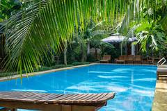 Holz-Sonnenliegen um einen Pool in einer Hotelanlage mit Villen auf der Insel Phu Quoc in Vietnam