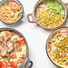Four bowls with fresh vegetable salads and food