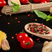 Spices, tomatoes, mushrooms and basil on a dark background with spaghetti