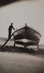 Photo of Grandfather, Alexander Cameron tarring his fishing boat, Susan Gardner, on Ardersier Beach