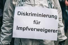 Anti-Corona-Demonstrant mit ABC Schutzanzug und Demoschild mit Botschaft: Diskriminierung für Impfverweigerer