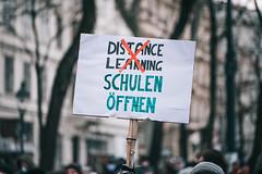 """Demoschild bei Anti-Corona-Demo mit durchstrichenem Text """"Distance Learning"""" und mit Botschaft """"Schulen öffnen"""""""