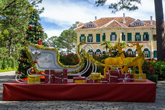 Goldene Rentiere, Weihnachtsbaum, Schlitten und Geschenke als Weihnachtsdekoration vor dem Bao Dai Königspalast in Da Lat, Vietnam