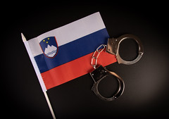 Violation of law, law-breaking concept. Metal handcuffs on Slovenian flag on black background top view