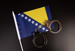 Violation of law, law-breaking concept. Metal handcuffs on flag of Bosnia and Herzegovina on black background top view