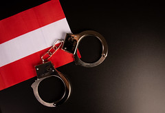Violation of law, law-breaking concept. Metal handcuffs on Austrian flag