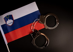 Violation of law, law-breaking concept. Metal handcuffs on Slovenian flag