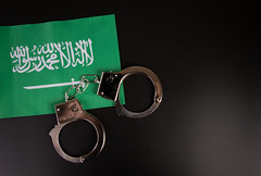 Violation of law, law-breaking concept. Metal handcuffs on flag of Saudi Arabia