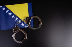 Violation of law, law-breaking concept. Metal handcuffs on flag of Bosnia and Herzegovina