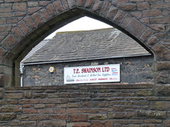 Photo of Got off a steam train in Penrith and there was this lovely arch framing the advert for T E Swainson Ltd