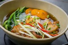 Japanisches Gericht Ramen Nudelsuppe mit frischem Gemüse, Chili und Schweinefleisch in einer Keramikschüssel Nahaufnahme