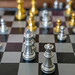 Close Up Photo of ongoing Chess Game on a Portable Magnetic Chess Board with Silver and Golden Chess Pieces