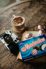 Munchmallow box on old book near coffee and old analog camera closeup.