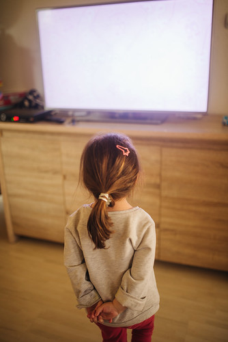 Little girl standing and watching television at home. Back view closeup.