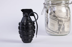 Black fragmentation Grenade and banknotes in a jar. Military industry, war, global arms trade, terrorism and crime concept.