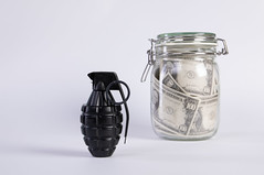 Black fragmentation Grenade and banknotes in a jar