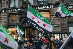 """Protesters on the street holding Syrian flags with message """"Free Syria"""""""