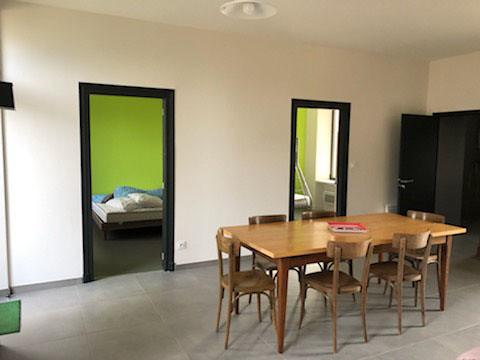 Gîte séjour avec deux chambres en arrière plan
