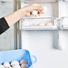 Woman holding a bowl of eggs and putting them into the refrigerator shelve
