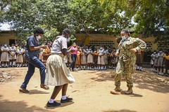 Lt. Aricka Faulkner learns a traditional dance from teachers and students at a junior high school in Tema, Ghana during Exercise Obangame Express 2021.