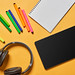 Notepad, colorful pens, headphones and tablet with empty screen