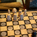 Close Up Photo of Vintage Chess Set with Hand Carved Stone Figures and Solid Wooden Chess Board