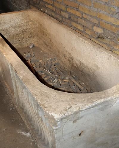 Carved stone sarcophagus with bones - crypt excavations, Basilica di San Crisogono, Rome.