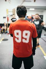 Man in a gym wearing a red jersey with number 99.