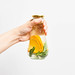 Female holds a glass bottle of infused water with lemon and mint