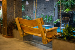 Wooden Bench Swing next to a Swimming Pool inside Chi House Hotel with many Plants and a Small Waterfall in Da Nang, Vietnam