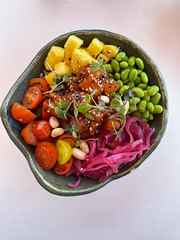 Top view of a bowl of healthy food on a white background: fruit, veggie, beans and herbs mix on Majorca
