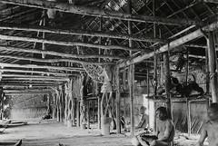 RV-10390-79 Gezicht in het mannenhuis van Amman, stroomopwaarts kijkend, met rechts voorouderpalen (bisjpalen) voor de vuurplaatsen. De eerste paal staat voor de centrale vuurplaats (mboijir). Jeu (Jö) Becembub. Foto Gerbrands 20 juli 1961