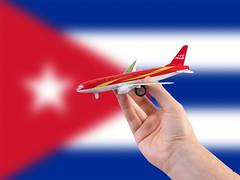 Cuba travel concept. Hand holding a miniature plane on national flag of Cuba