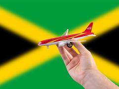 Jamaica travel concept. Hand holding a miniature plane on national flag of Jamaica